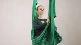 做反地心引力的飞行瑜伽的年轻白种人妇女在吊床行使在演播室户内 空中航空飞行健身 股票视频