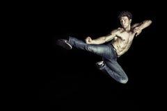 做反撞力跳跃的武术运动员 免版税库存照片