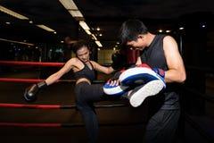 做反撞力锻炼的女孩在与个人教练员的kickboxing的训练期间 免版税图库摄影