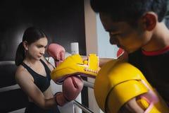 做反撞力锻炼的女孩在与个人教练员的kickboxing的训练期间 免版税库存图片