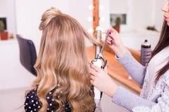 做发型的妇女美发师使用年轻女性的长的头发的烫发钳 免版税库存图片