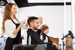 做发型的愉快的美发师 免版税图库摄影