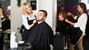 做发型的愉快的美发师 图库摄影