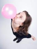 做口香糖气球的俏丽的女孩 库存图片