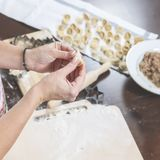 做可口自创饺子的过程 在厨房用桌上放置装填、立即可食的饺子和面团 库存图片
