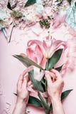 做可爱的桃红色百合的女性手开花在淡色桌上的花束用卖花人装饰设备,顶视图 创造性的Floris 库存照片
