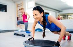 做各种各样的锻炼的健身房的两名适合的可爱的妇女 图库摄影