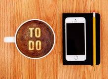 做名单与智能手机和笔记薄的拿铁艺术木表面上 库存照片