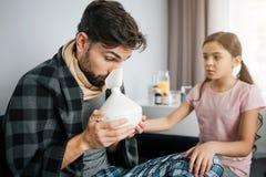 做吸入做法的病的年轻人 他拿着特别设备fo这 担心的小女孩除他以外坐在一个 库存图片