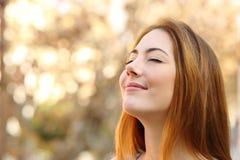 做呼吸的美丽的妇女行使有秋天背景 免版税图库摄影
