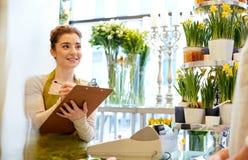 做命令的卖花人妇女和人在花店 免版税图库摄影