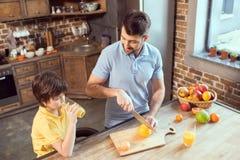 做和喝新鲜的汁液的父亲和儿子 免版税库存照片