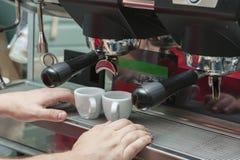 做咖啡咖啡机器,男服务员` s手 免版税库存照片