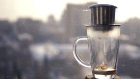 做咖啡在亚洲,落入的下落一个玻璃碗 以在的城市` s春天风景为背景 库存照片
