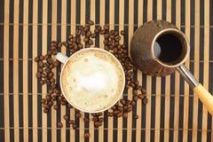 做咖啡在咖啡豆背景  库存图片