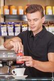 做咖啡的英俊的年轻barista。 免版税图库摄影