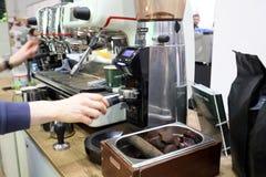 做咖啡的Barista在咖啡机器在Gastrofood -食物的承办宴席的商品交易会和饮料在克拉科夫 波兰 免版税库存照片