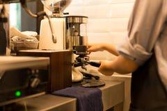 做咖啡的Barista研新近地烤咖啡豆 库存照片