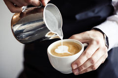 做咖啡,倾吐的牛奶的男服务员 免版税库存照片