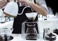 做咖啡,Barista倾吐的滴水咖啡的Barista到玻璃里 库存图片