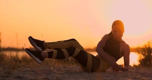 做咬嚼的健身妇女在海滩 做咬嚼的健身妇女行使往海滩的锻炼 女性适合 股票视频