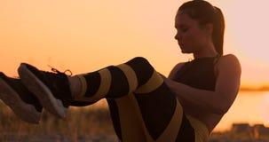 做咬嚼的健身妇女在海滩 做咬嚼的健身妇女行使往海滩的锻炼 女性适合 股票录像