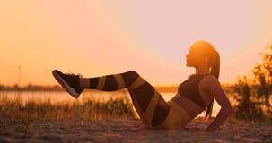 做咬嚼的健身妇女在海滩 做咬嚼的健身妇女行使往海滩的锻炼 女性适合 影视素材