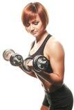 做哑铃卷毛的年轻女运动员 免版税图库摄影