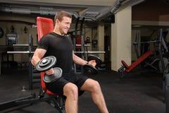做哑铃在健身房的年轻人二头肌锻炼 库存照片