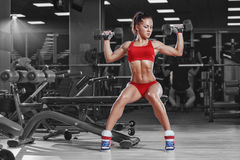 做哑铃的性感的年轻竞技女孩按锻炼坐在健身房的长凳 图库摄影