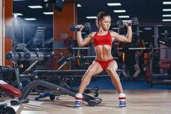 做哑铃的性感的年轻竞技女孩按锻炼坐在健身房的长凳 库存照片