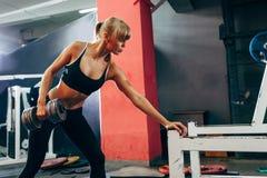 做唯一胳膊哑铃行的健身房的妇女 免版税库存图片
