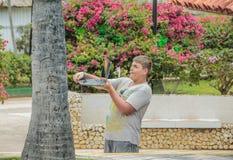 做图片的十几岁的男孩在他的膝上型计算机在热带庭院里 免版税库存图片