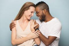 做图片的愉快的不同的夫妇拥抱画象在演播室 库存照片