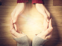 做圈子用手的妇女和人 里面温暖的光 免版税库存图片