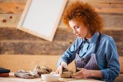 做土制盘的创造性的少妇陶瓷工在车间 免版税库存图片