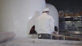 做土耳其阿拉伯食物fatayer的白色制服的厨师在现代餐馆厨房里 人采取从桌的面团和 影视素材
