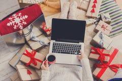 做圣诞节在网上购物与膝上型计算机的妇女,在看法上 图库摄影