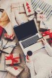 做圣诞节在网上购物与膝上型计算机的妇女,在看法上 库存照片