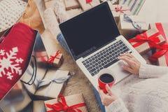 做圣诞节在网上购物与膝上型计算机的妇女,在看法上 免版税图库摄影