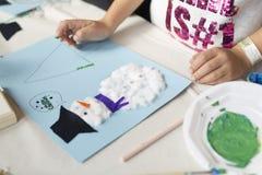 做圣诞节工艺的一个十岁的女孩的手 免版税库存图片