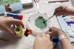做圣诞节工艺的一个十岁的女孩的手 免版税图库摄影