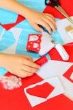 做圣诞节工艺的孩子 孩子在桌上把他的手放 五颜六色的毛毡房子装饰品 材料和工具 免版税图库摄影