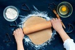 做圣诞节曲奇饼的妇女面团 免版税库存图片