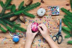 做圣诞节球的女孩别住在球上的衣服饰物之小金属片 免版税图库摄影