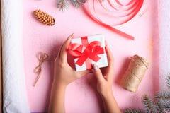做圣诞节礼物的女孩的顶视图在桌背景 手工制造礼物 创造性的爱好概念 免版税库存图片