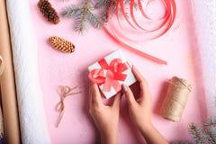 做圣诞节礼物的女孩的顶视图在桌背景 手工制造礼物 创造性的爱好概念 图库摄影