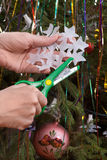 做圣诞节纸雪花的手在圣诞树backgr 图库摄影