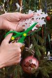 做圣诞节纸雪花的手 免版税库存照片