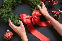 做圣诞节花圈的卖花人手 免版税库存照片